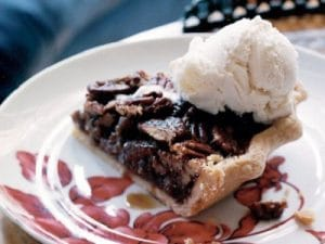 slice of texas pecan pie with scoop of ice cream of top
