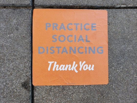 practice social distancing sign on sidewalk outside of whataburger