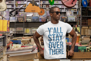 man wearing sunglasses and y'all stay over there t-shirt in a music store