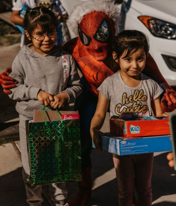 happy kids pose with spider-man santa on christmas day