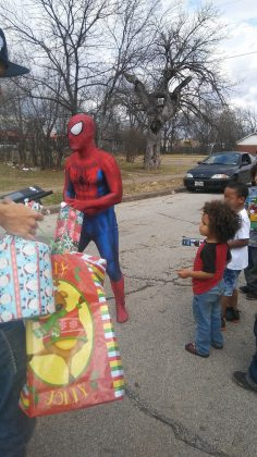 spider-man santa giving out toys to kids on christmas