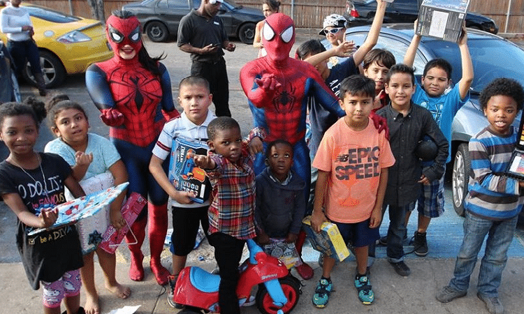spider-man santa and a group of kids he gave gifts to