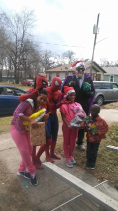 spider-man santa and helpers take pictures with kids on christmas day