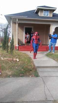 spider-man santa leaving a house after giving kids gifts on christmas