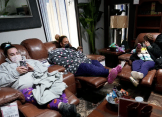 family sitting in a furniture store with masks on due to Texas winter storm
