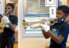 young Texas boy / student plays his band new trumpet at school in Houston