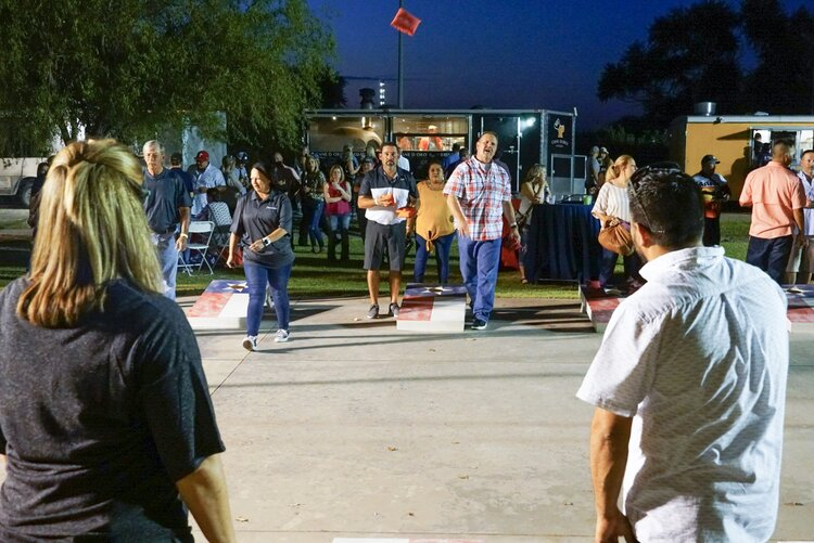 Texan people standing outside by food trucks playing a game of cornhole