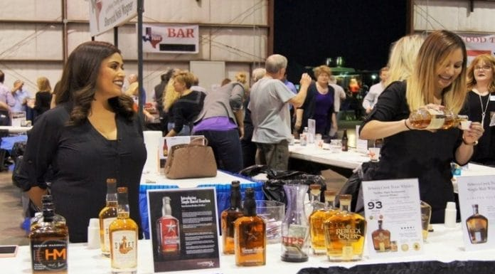 two women standing at a table providing alcohol tastings